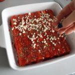 3. Rurki przełożyć donaczynia żaroodpornego, posmarować sosem iposypać serem